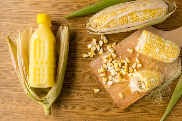 Top view of fresh sweet corn and corn milk on wooden table.