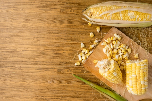 Top view of fresh sweet corn on wooden table.