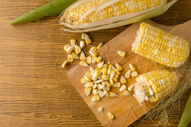 Top view of fresh sweet corn on wooden table
