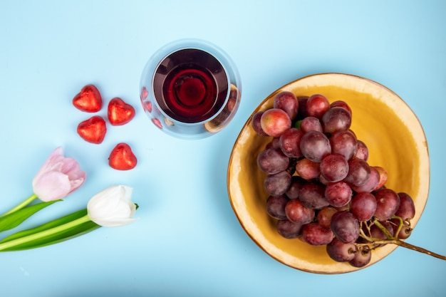 Top view of fresh sweet grape in a bowl with white and pink color tulips, a glass of wine and heart shaped chocolate candies in red foil scattered on blue table