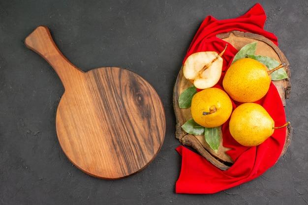 Vista dall'alto pere dolci fresche su tessuto rosso e colore fresco maturo da scrivania scuro morbido