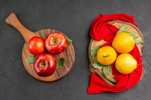 ダークグレーのテーブルにリンゴと新鮮な甘い梨の上面図赤熟した新鮮なまろやかな木