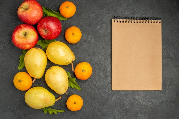 Top view fresh sweet pears with tangerines and apples on grey background