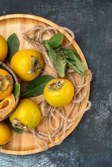 Vista dall'alto cachi dolci freschi su un tavolo scuro gustano frutta matura