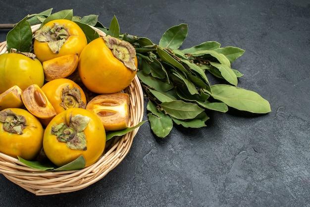 Cachi dolci freschi di vista superiore all'interno del canestro sui frutti pastosi del pavimento scuro maturi
