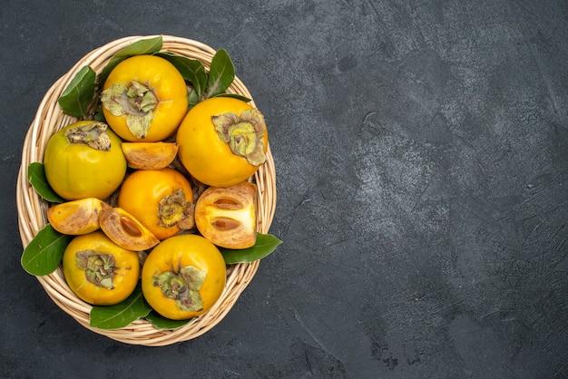 Вид сверху свежей сладкой хурмы внутри корзины на темном фруктовом спелом вкусе