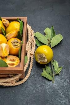 Вид сверху свежей сладкой хурмы внутри коробки на темном столе со вкусом спелых фруктов