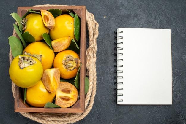 暗い床の箱の中の新鮮な甘い柿の上面図熟した果実を味わう