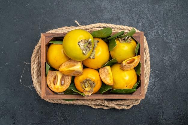 어두운 테이블에 상자 안에 상위 뷰 신선한 달콤한 감 맛 익은 과일