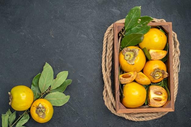 暗いテーブルのボックス内の新鮮な甘い柿の上面図熟した果実の味