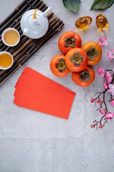 Top view of fresh sweet persimmons kaki with leaves on gray table for chinese lunar new year concept, the word means spring is coming.