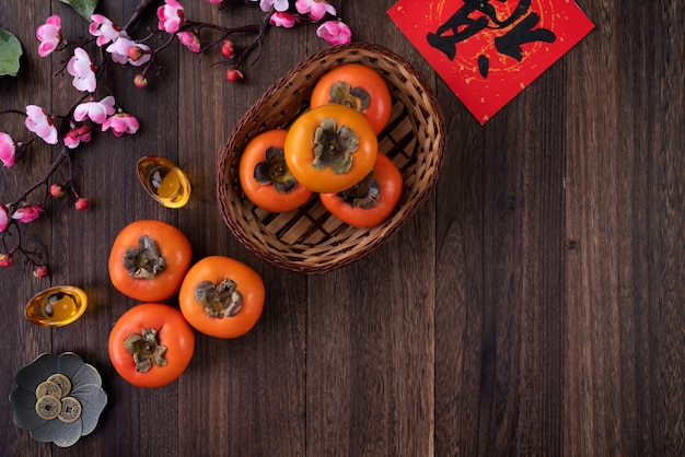 Top view of fresh sweet persimmons kaki with leaves on wooden table background