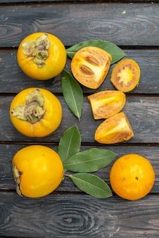 木製の素朴なテーブル、フルーツ熟したまろやかな上から見た新鮮な甘い柿