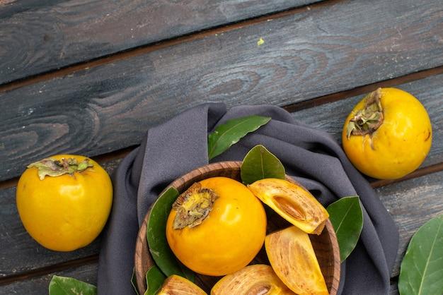 上面図木製テーブルの新鮮な甘い柿、熟した果実のまろやか