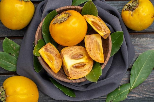 木のテーブルの上の新鮮な甘い柿、熟した果物のまろやかな上面図
