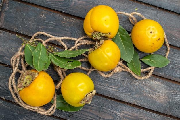 木のテーブルの上の新鮮な甘い柿、熟したフルーツの味