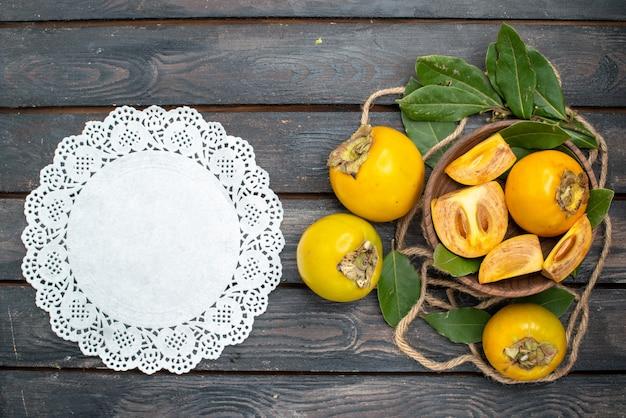 木製の素朴なテーブルの上の新鮮な甘い柿の上面図、熟した果物を味わう