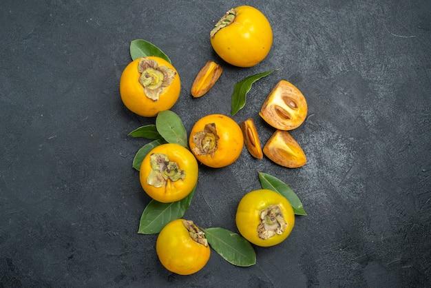暗いテーブルの上に葉を持つ新鮮な甘い柿の上面図熟した果実の味