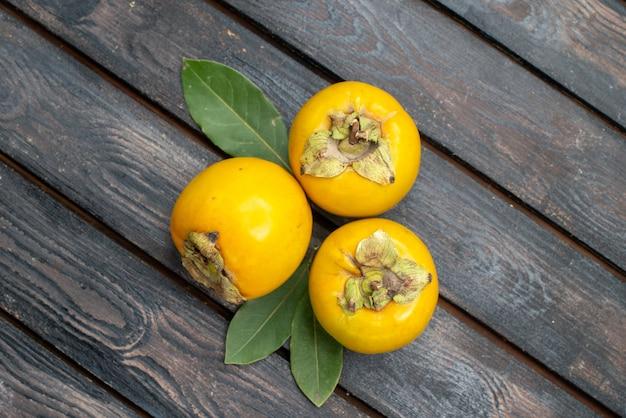 Vista dall'alto cachi dolci freschi sulla tavola rustica in legno, frutta pastosa