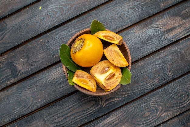 Vista dall'alto cachi dolci freschi su un tavolo rustico in legno, dolce salute della frutta