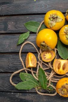 Vista dall'alto cachi dolci freschi su un tavolo rustico in legno, frutta pastosa