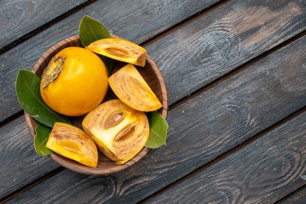 Vista dall'alto cachi dolci freschi sul tavolo rustico in legno, frutta pastosa