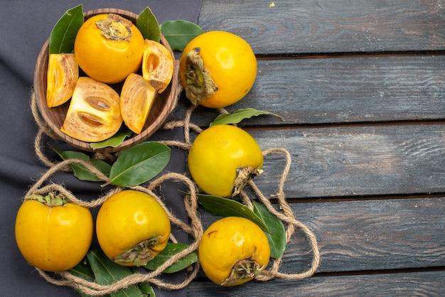 Vista dall'alto cachi dolci freschi sulla tavola rustica in legno, frutta matura