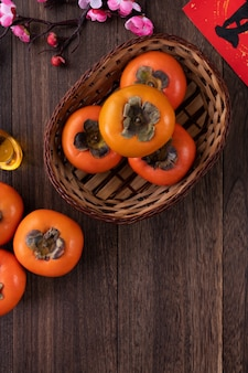 Top view of fresh sweet persimmons on wooden table background for chinese new year design