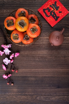 Top view of fresh sweet persimmons on wooden table background for chinese new year