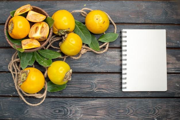 Vista dall'alto cachi dolci freschi su un tavolo di legno, gusto di frutta matura