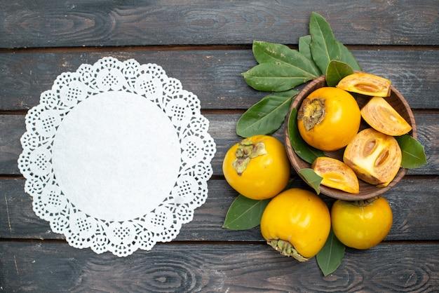 Vista dall'alto cachi dolci freschi sulla tavola di legno, frutta matura mellow