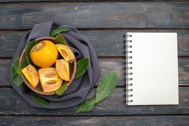 Vista dall'alto di cachi dolci freschi su un tavolo di legno, frutta dolce salute
