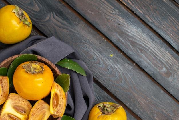 Vista dall'alto cachi dolci freschi su un tavolo di legno, frutta matura pastosa