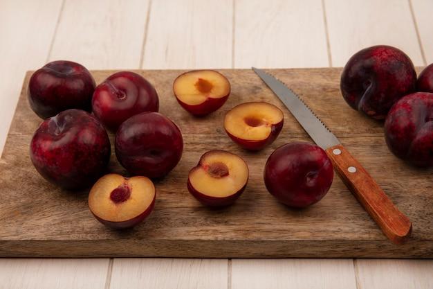 Vista dall'alto di trame fresche e dolci su una tavola da cucina in legno con coltello su una parete in legno beige