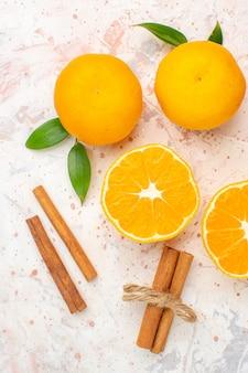 Vista dall'alto mandarini freschi bastoncini di cannella sulla superficie luminosa