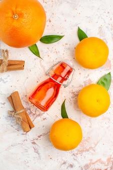 Vista dall'alto mandarini freschi bastoncini di cannella bottiglia arancione sulla superficie luminosa