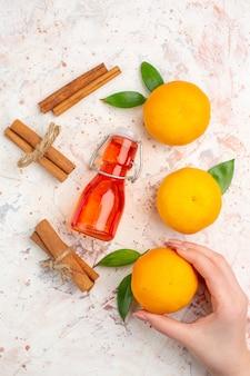 Vista superiore mandarini freschi bastoncini di cannella mandarino in mano femminile bottiglia sulla superficie luminosa
