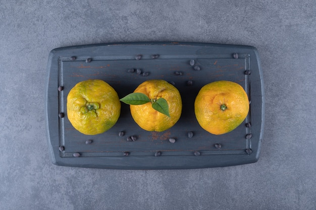 Vista dall'alto di mandarini freschi sul bordo di legno grigio.