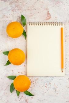 Mandarini freschi di vista superiore una matita arancione del taccuino sulla superficie isolata luminosa