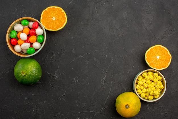 Vista dall'alto di mandarini freschi con caramelle sul tavolo nero