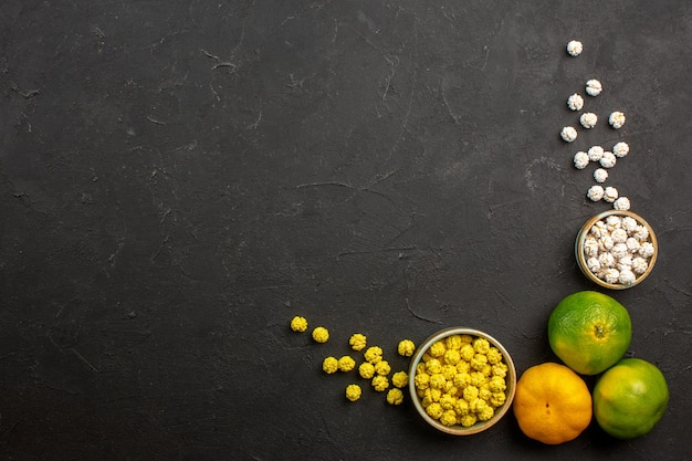 Top view of fresh tangerines with candies on grey table