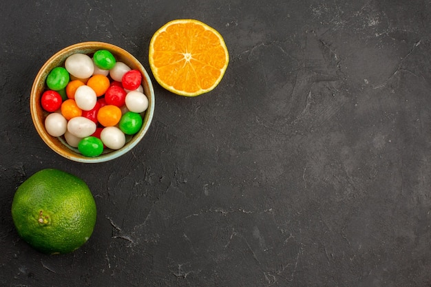Top view of fresh tangerines with colorful candies on black table