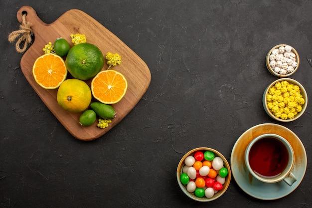 Vista dall'alto di mandarini freschi con una tazza di tè e caramelle sul nero