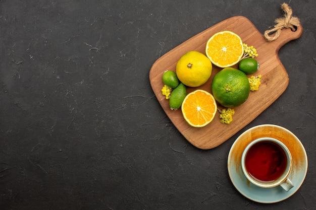 Vista dall'alto di mandarini freschi con feijoa e tazza di tè su nero