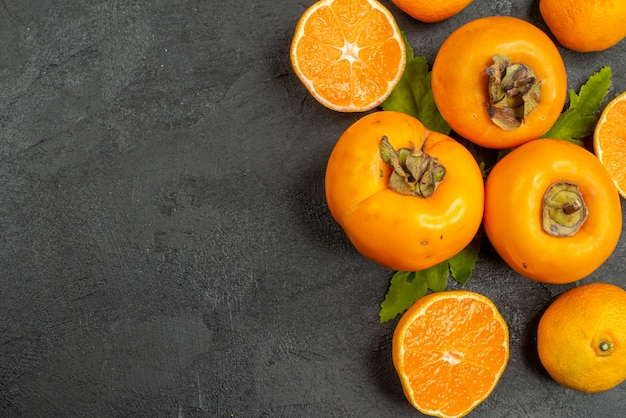 Top view fresh tangerines with persimmons on a grey background