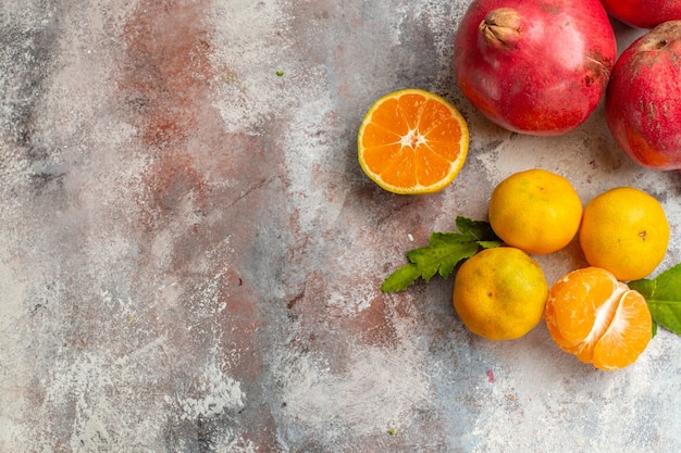 Top view fresh tangerines with pomegranates on light background