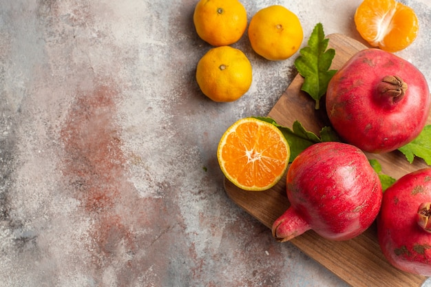 Top view fresh tangerines with red pomegranates on light background