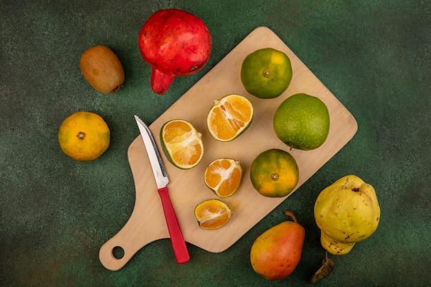 Vista dall'alto di mandarini freschi su una tavola da cucina in legno con coltello con deliziosi frutti come il melograno pera