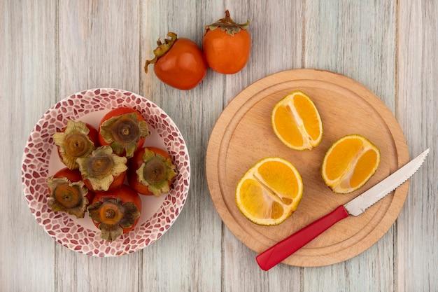 Vista dall'alto di mandarini freschi su una tavola da cucina in legno con coltello con cachi su una ciotola su un fondo di legno grigio