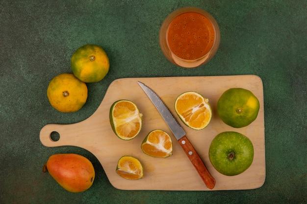 Vista dall'alto di mandarini freschi su una tavola da cucina in legno con coltello con succo di mandarino su un bicchiere